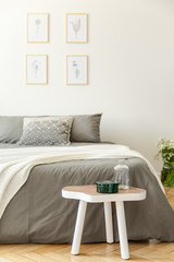 White wooden table in front of grey bed in minimal bedroom interior with posters. Real photo