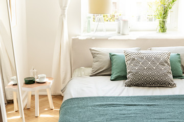 Pillows and green sheets on bed in bedroom interior with white table next to mirror. Real photo