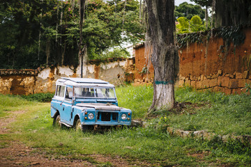 An old blue 4x4 stands under a gigantic tropical tree, Barichara/ Colombia/ South America