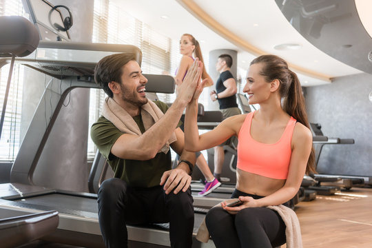 Cheerful young man and woman giving high five after a successful workout session in a modern fitness club
