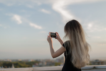 Girl taking photos from the roof at sunset on smartphone