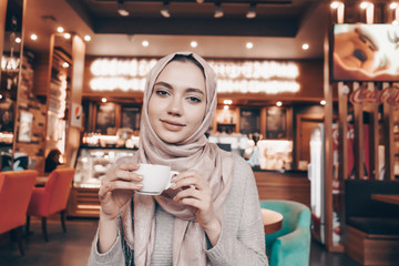 nice Arab girl with a headscarf on her head dines in a cozy cafe, drinks fragrant tea