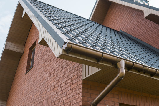 Modern roof covered with tile effect PVC coated brown metal roof sheets.