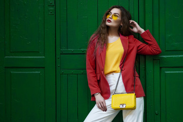 Outdoor fashion portrait of young beautiful woman wearing blazer, yellow sunglasses, blouse, white trousers, holding small quilted bag, posing near the green door. copy,empty  space for text