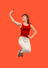 Full length of pretty young woman with mobile phone while jumping