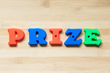 Color plastic alphabet in word prize on wood background