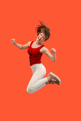 Freedom in moving. Pretty young woman jumping against orange background