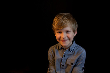 Smiling boy. He looks at you. He looks at the camera. Smile. Black background. Isolated.