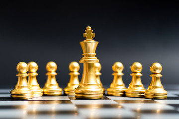Gold king chess piece stand in front of pawn on black background (Concept of leadership, management)
