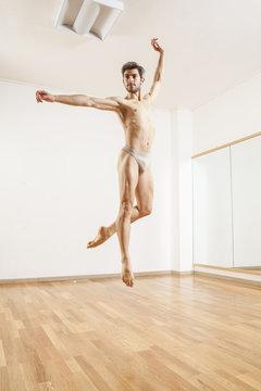 Young beautiful male  ballett dancer jumping in studio