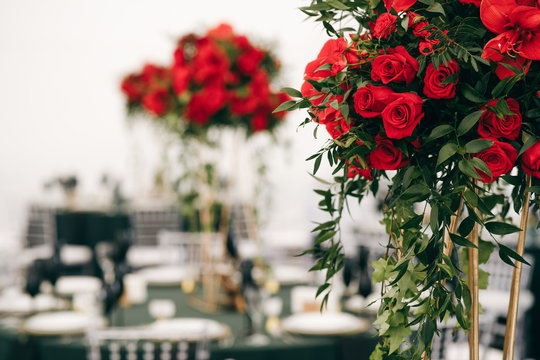 Tall bouquets of roses stand on dark green tables in restaurant hall
