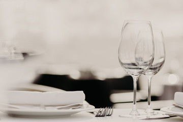 Photo of luxury empty wineglasses, forks and plates on white tablewear against blurred background. Dinner table in pastel tones. Restaurant setting