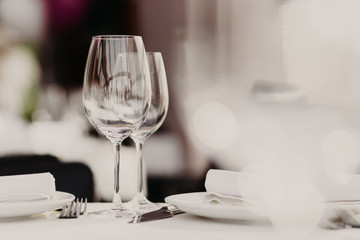 Served restaurant table with cutlery and wine glasses against blurred background. Banquet table for guests. Festive event. Cozy atmosphere. Catering cafe service