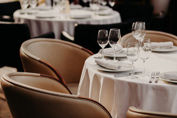 Horizontal shot of served round table with white tableclothes, wineglasses, plates, forks and knives, two armchairs near. Cozy atmosphere in luxury restaurant.