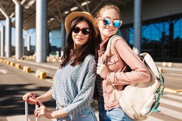 Portrait of pretty smiling girls in sunglasses happily looking in camera with backpack on shoulder and airport on background