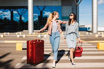Beautiful stylish girls in sunglasses happily walking along pedestrian strip with suitcases and airport on background