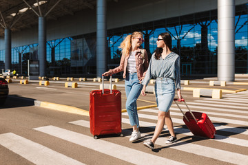 Pretty stylish girls in sunglasses joyfully walking along pedestrian strip with suitcases and airport on background