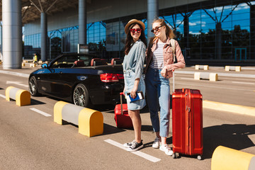 Beautiful girls in sunglasses joyfully looking in camera with red suitcases and cabriolet on background