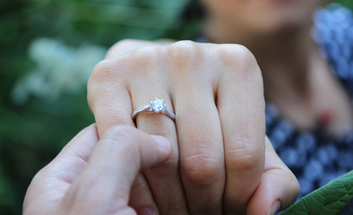 Picture of man putting engagement silver ring on woman hand, outdoor