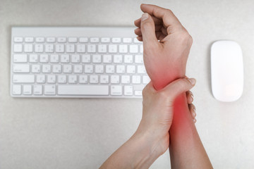 A woman feels a pain in her wrist using her computer mouse.