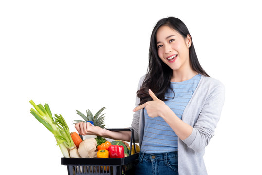 Asian woman holding shopping basket full of vegetables and groceries