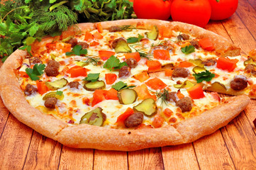 Pizza with meat, cucumbers, tomatoes and greens