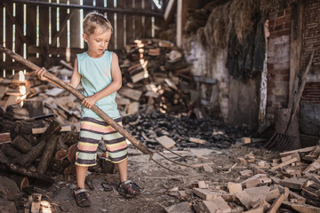 Little boy working in a shed with pitchfork