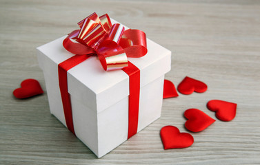 white gift box on a gray background and textile heart shapes