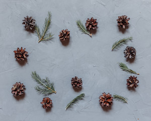 Christmas background with fir tree and decor, branches and cones. Top view with copy space, gray plastered background