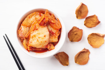Kimchi cabbage in a bowl with chopsticks, top view, Korean food