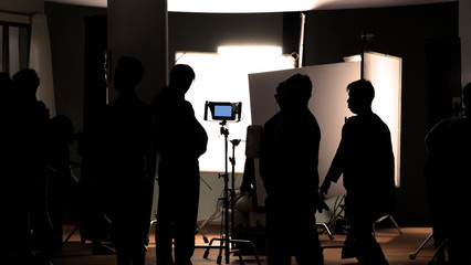 Video production behind the scenes which film crew team in silhouette shooting or recording tv movie commercial with professional equipment such as high definition 4k camera with monitor in studio set