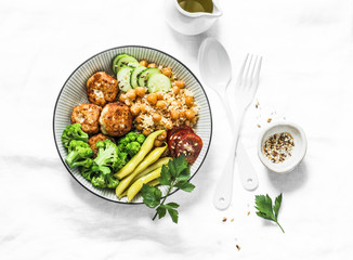 Healthy balanced buddha bowl lunch - spicy couscous with chickpeas, broccoli, green beans and turkey meatballs on light background, top view. Flat lay