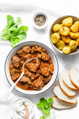 Irish beef stew and turmeric potatoes - delicious seasonal lunch on a light background, top view. Flat lay