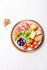 Antipasto Plate with dried bread, ham serrano, tomato cherry and purple olives. White background.