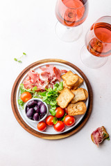 Antipasto Plate with dried bread, ham serrano, tomato cherry and purple olives. White background.