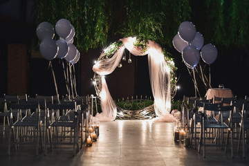 Shine wedding altar for newlyweds stands on the backyard decorated with balloons and greenery