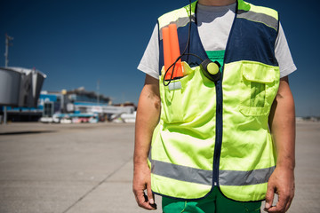 Work clothing. Close up of male torso in signaling vest. Airport terminal, runway and blue sky on blurred background