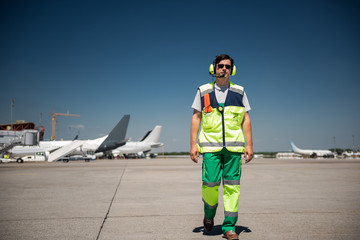 I am coming. Full length portrait of aviation marshaller walking down the runway. Man wearing sunglasses and headphones