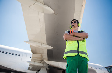 Enjoying sunny day. Low angle portrait of smiling man in sunglasses standing under airplane wing