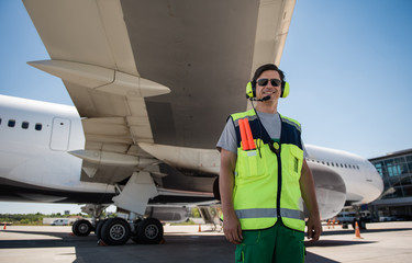 I love my job. Smiling man in sunglasses standing at airdrome. Blue sky and aircraft with open cargo door on background
