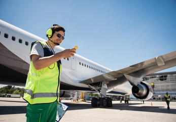 Chatting during work. Smiling man in sunglasses looking at cellphone and holding clipboard. Runway, passenger plane and colleague on background