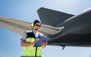 Filling out documents. Waist up portrait of serene man in sunglasses noting data. Blue sky, aircraft wing and tail in the background