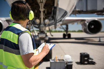 Focusing on work. Back view of ground crew member noting data on clipboard while checking aircraft before the flight