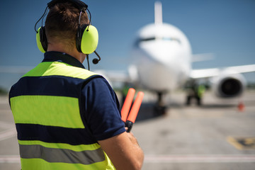 Meeting aircraft. Back view of aviation marshaller observing commercial jet and waiting for signaling