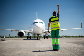 Nice to see you. Back view of aviation marshaller doing job at airport. Sky, modern aircraft and runway on background