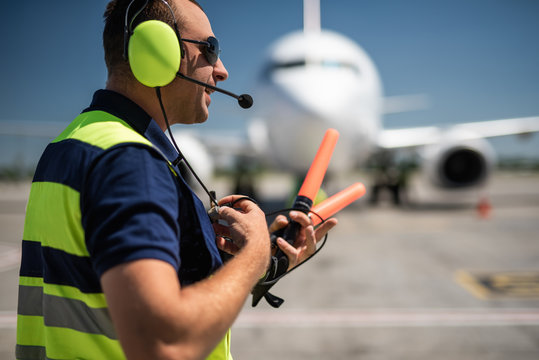 Important conversation. Side view of aviation marshaller talking on portable radio