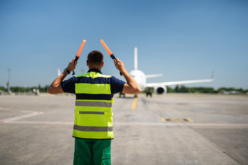 Directing the jet. Back view of aviation marshaller at airport. Aircraft, runway and sky on blurred background