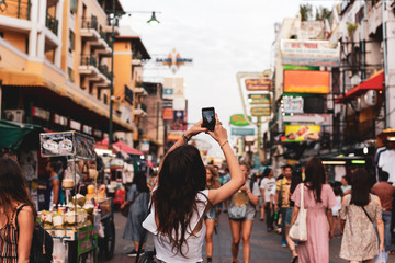 Woman tourist taking pictures with her cell phone on street in blurred background.