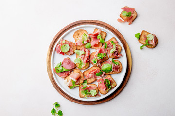 Mini open sandwiches with jamon serrano on white plate