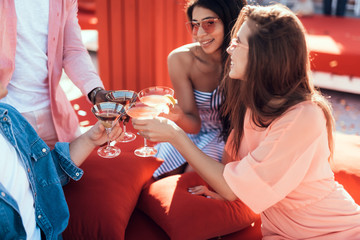 Outgoing women clanging glasses of cocktail with males during positive conversation. Satisfied comrades during rest concept